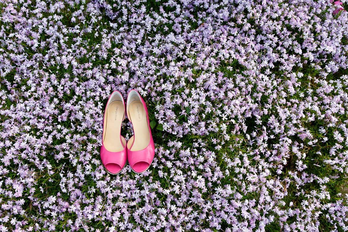 Trouwschoenen in een bloemenveld
