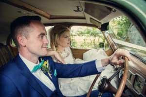 Bruid en bruidegom in trouwauto