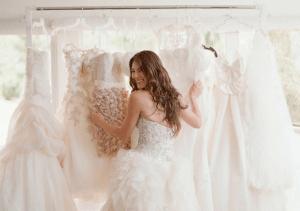 Bruids kiest uit rek vol trouwjurken