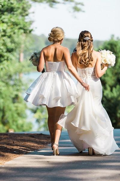 Ceremoniemeester houdt jurk bruid vast