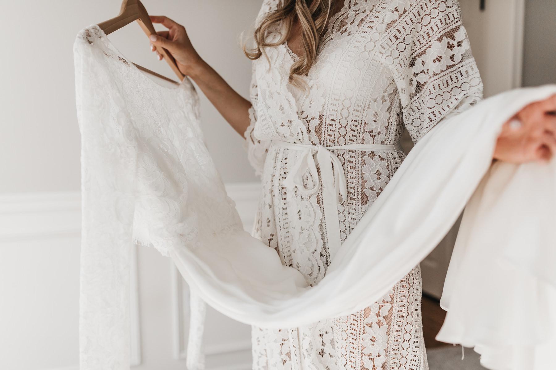 Bruid met haar trouwjurk in haar handen