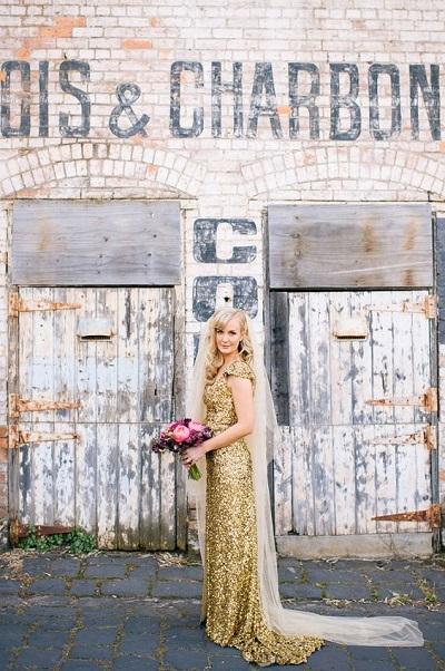 Bruid in gouden trouwjurk met sluier