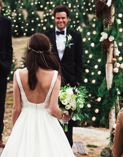 Bruid en bruidegom tussen kerstbomen