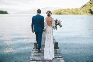 Bruid met doorschijnende trouwjurk naast bruidegom