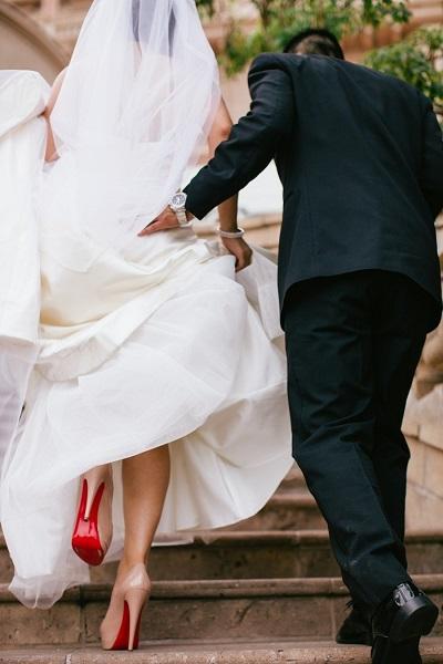 Bruid met hoge hakken en opgetilde trouwjurk