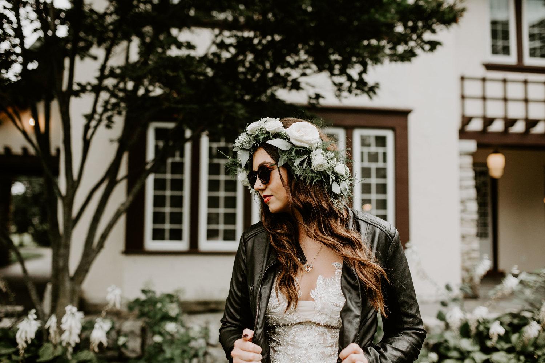 Bruid met leren jasje over haar trouwjurk