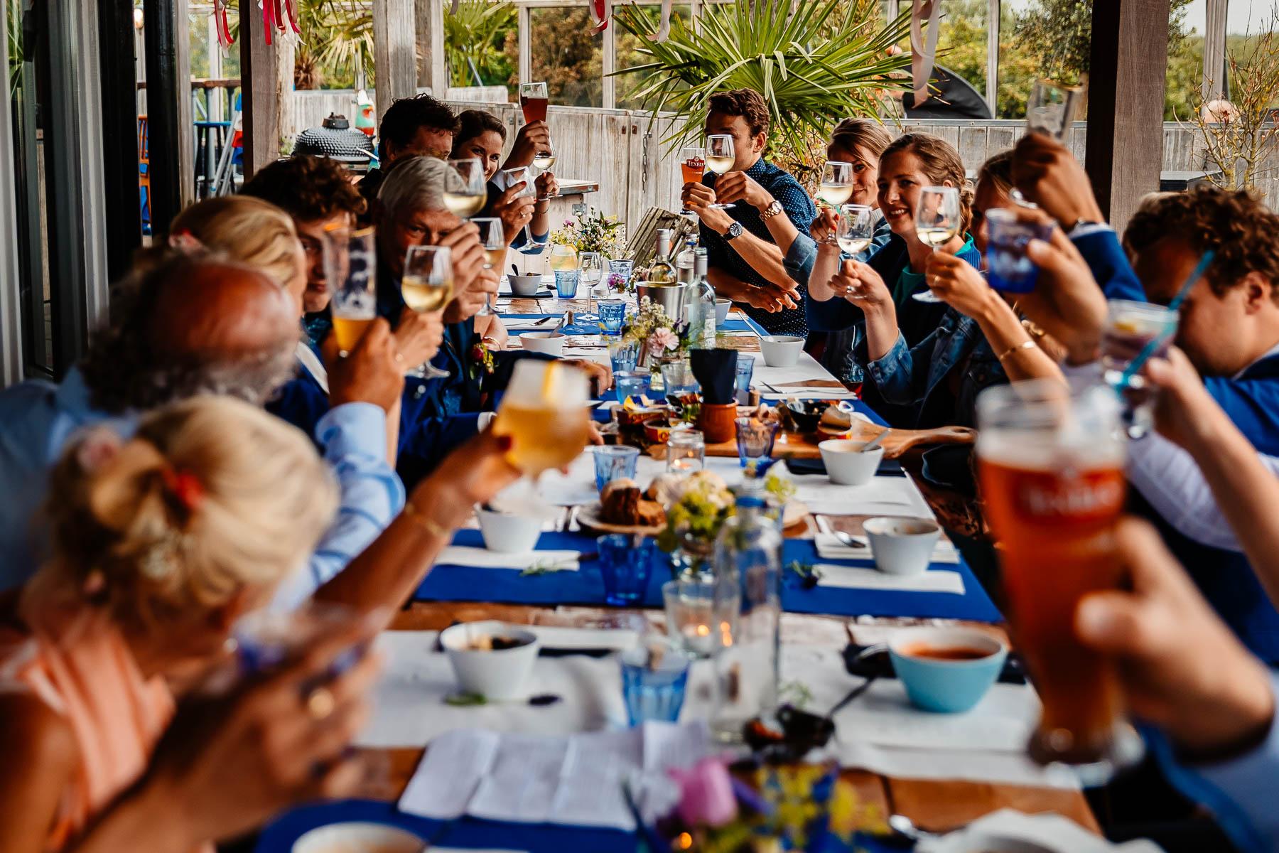 Gasten aan tafel met drankje in hun handen