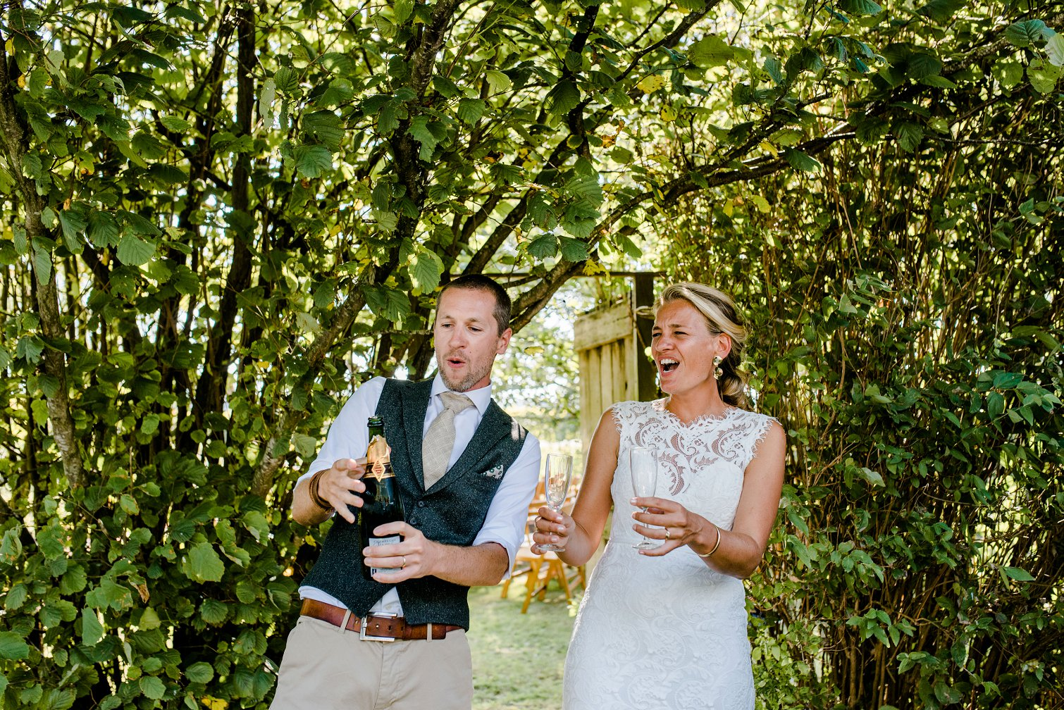Bruidspaar met fles champagne in hun handen