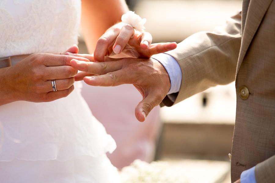 Bruid schuift trouwring om hand bruidegom