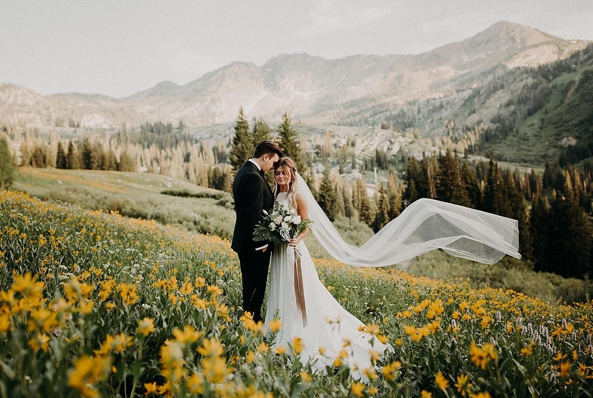 Bruidspaar in een veld met bloemen