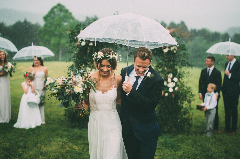 Bruidspaar onder paraplu op bruiloft