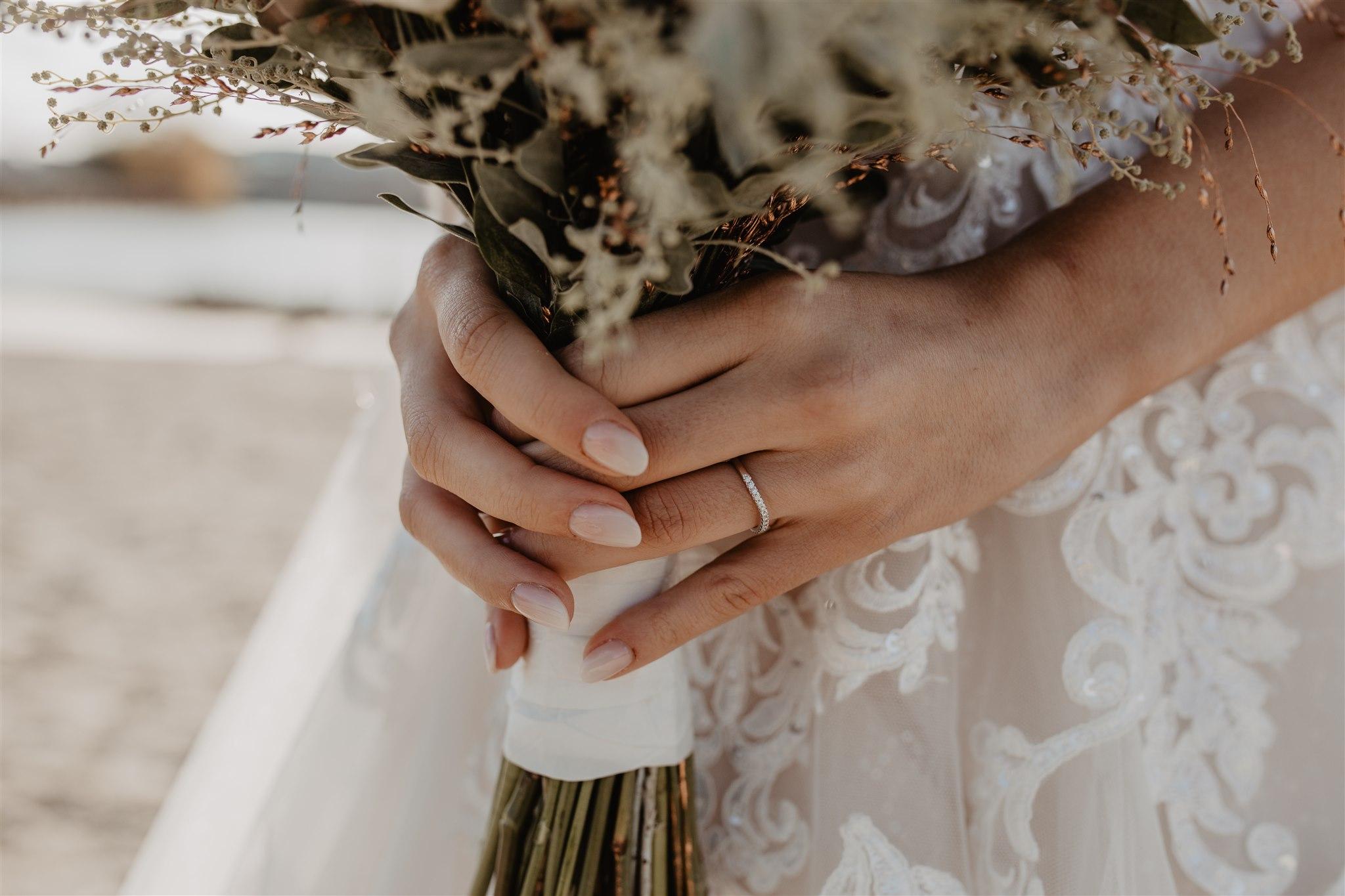 Handen van de bruid met bruidsboeket